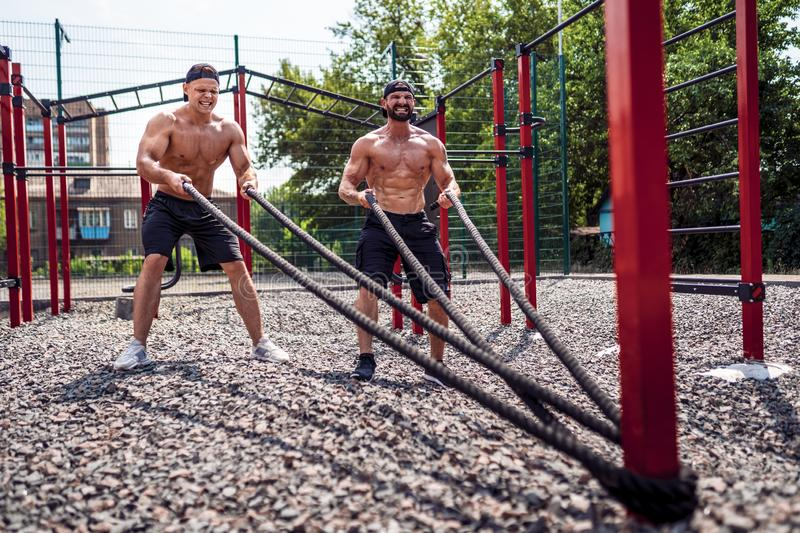 Men work hard with rope at street gym yard. Strength and motivation. Outdoor workout. fitness, sport, exercising royalty free stock photo