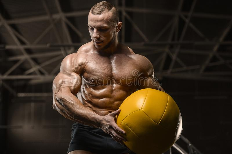 Athletic men workout with ball fitness exercises. Handsome athletic man pumping up muscles workout with ball fitness exercises and bodybuilding concept stock photo