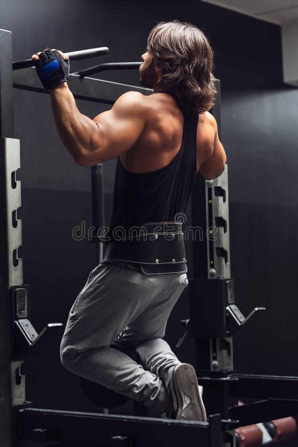 Athletic muscular man doing pull-ups in a gym. Athletic muscular man working out doing pull-ups in a gym viewed from the rear to strengthen his muscles royalty free stock image