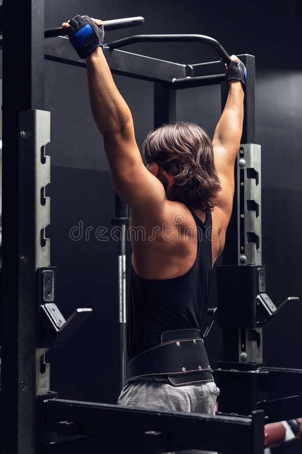 Athletic muscular man doing pull-ups in a gym. Athletic muscular man working out doing pull-ups in a gym viewed from the rear to strengthen his muscles royalty free stock photos