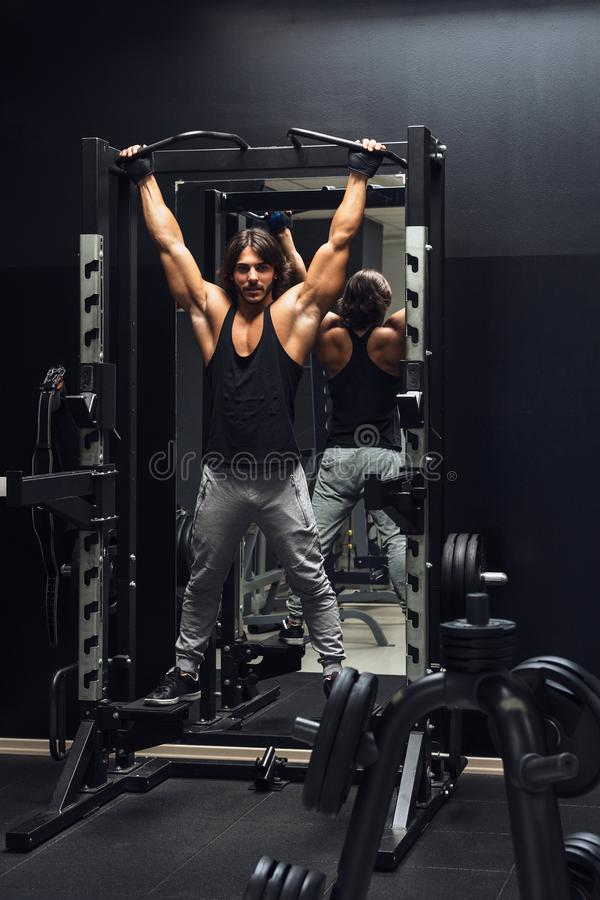Athletic muscular man doing pull-ups in a gym. Athletic muscular man working out doing pull-ups in a gym to strengthen his muscles royalty free stock photo