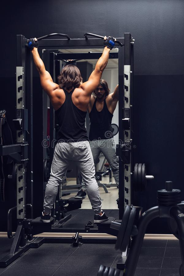 Athletic muscular man doing pull-ups in a gym. Athletic muscular man working out doing pull-ups in a gym viewed from the rear to strengthen his muscles stock photography