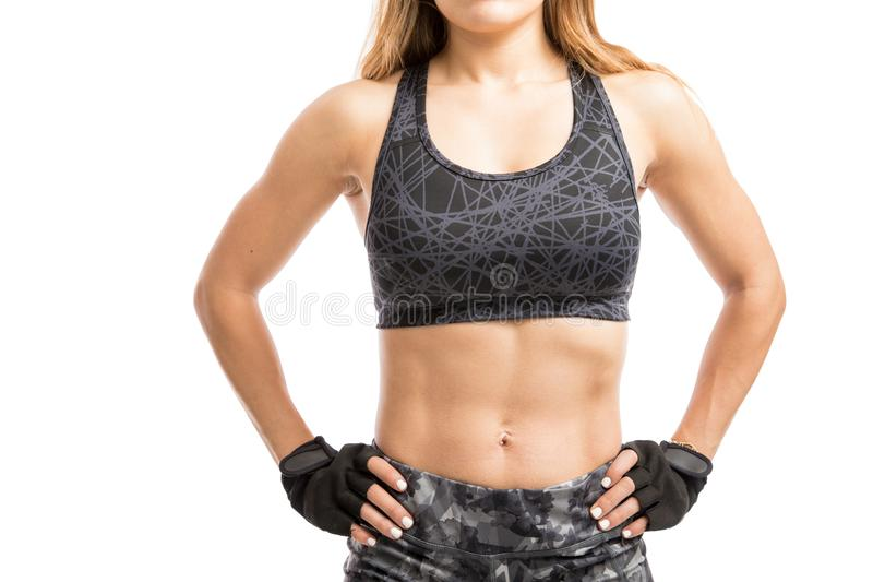 Closeup of a woman with abs. Athletic and muscular woman with toned abs in a sporty outfit, seen up close stock photography