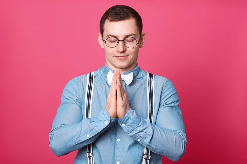 Athletic peaceful young man stands with closed eyes, puts palms of his hands together, prays with smile on his face. Handsome calm royalty free stock image