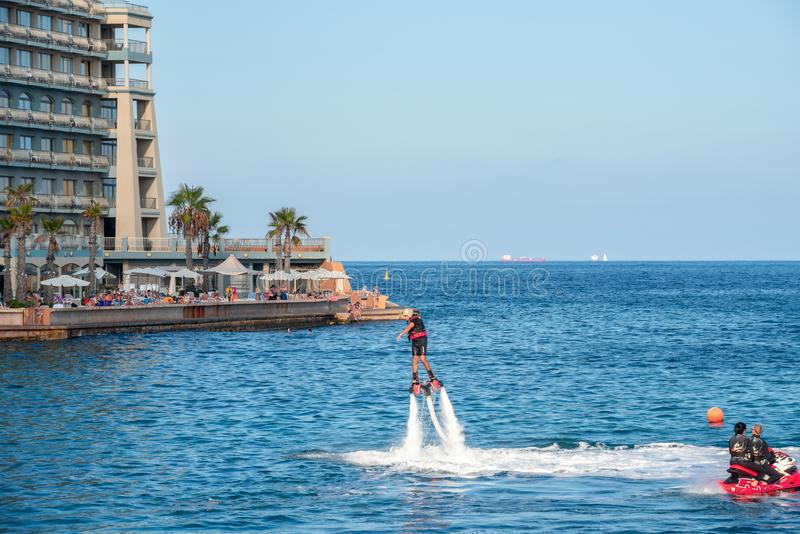 Athletic people practicing  new extreme water sport called flyboard. Malta. ST JULIAN'S BAY, MALTA - OCTOBER 06, 2014: New popular type of extreme water royalty free stock photography