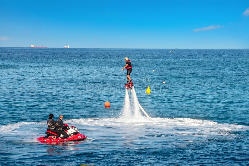 Athletic people practicing  new extreme water sport called flyboard. Malta. ST JULIAN'S BAY, MALTA - OCTOBER 06, 2014: New popular type of extreme water stock photo
