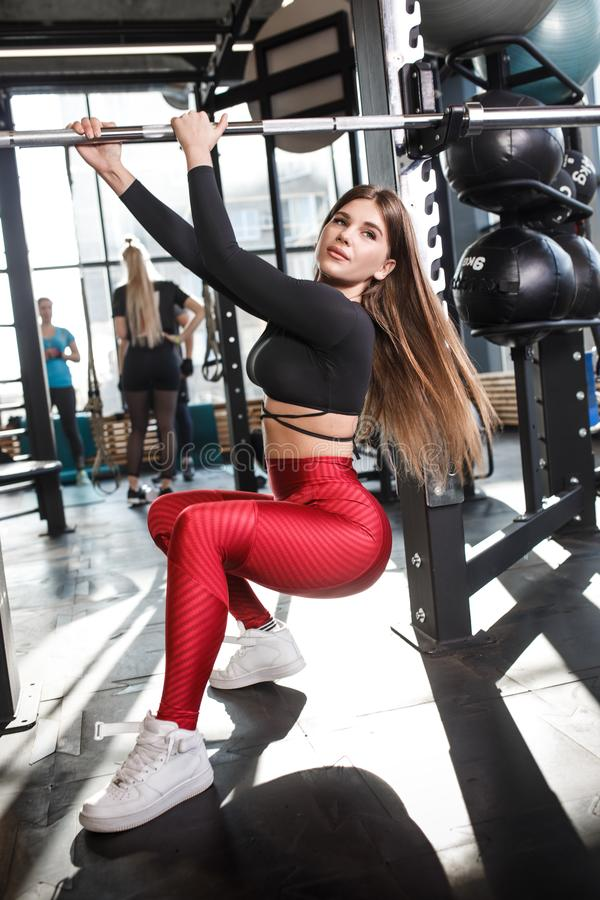 Athletic pretty girl in stylish bright sports clothes poses next to the horizontal bar in the modern gym royalty free stock photos