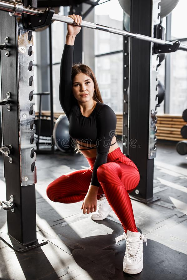 Athletic pretty girl in stylish bright sports clothes poses next to the horizontal bar in the modern gym royalty free stock image