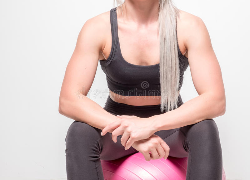 Athletic and ripped looking blonde female in a studio. Isolated studio image of an athletic blond female with attitude royalty free stock photography