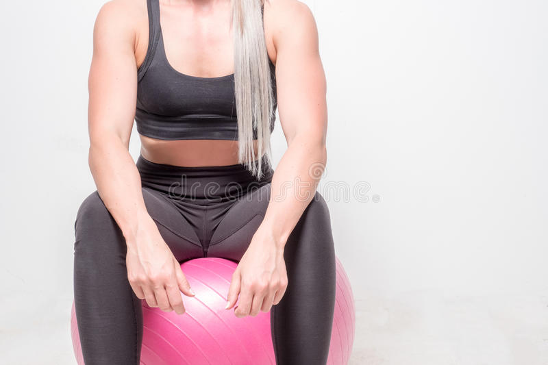 Athletic and ripped looking blonde female in a studio. Isolated studio image of an athletic blond female with attitude royalty free stock images