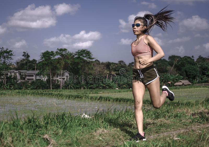 Athletic runner Asian woman training running series workout working hard outdoors on field background in harsh contrast light spor stock photos