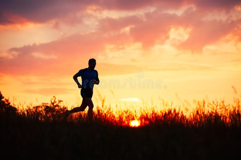 Athletic runner at the sunset stock image