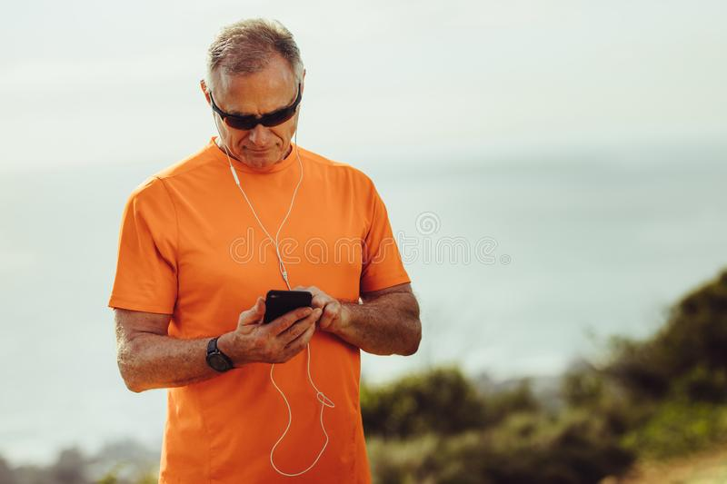 Athletic senior man listening to music during workout royalty free stock images