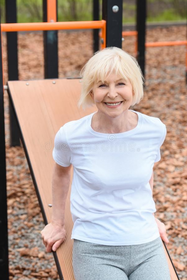 athletic senior woman smiling and exercising stock images