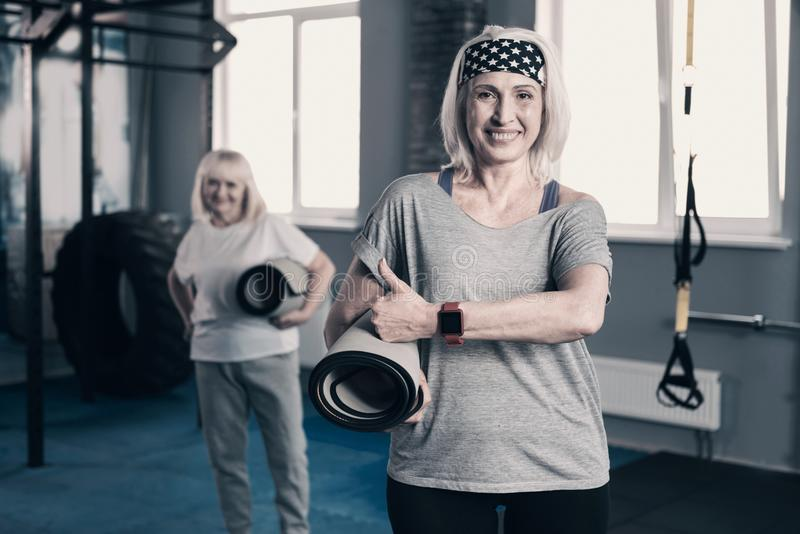 Athletic senior woman with yoga mat giving thumbs up royalty free stock photography