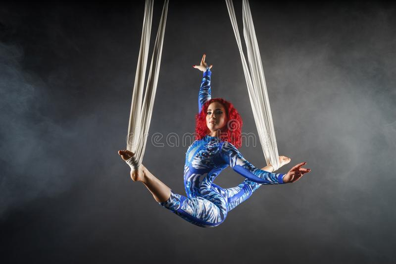 Athletic aerial circus artist with redhead in blue costume dancing in the air with balance stock photo