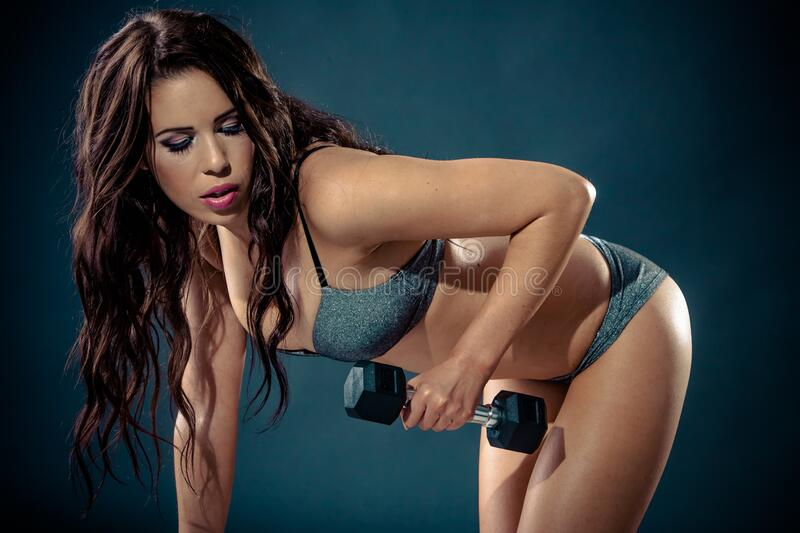 Athletic sexy young woman working out in studio, swimwear royalty free stock photo