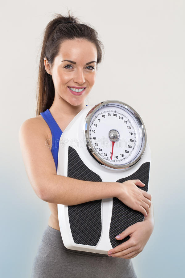 Athletic smiling young woman holding a weight scale royalty free stock photo