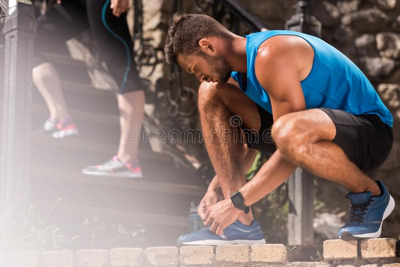 Sportsman tying shoelaces. Athletic sportsman tying shoelaces on sneakers royalty free stock image