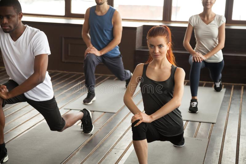 Sporty diverse people doing lunge forward exercise at group trai. Athletic sporty diverse people doing lunge fitness exercise step forward warming up at strength royalty free stock photo