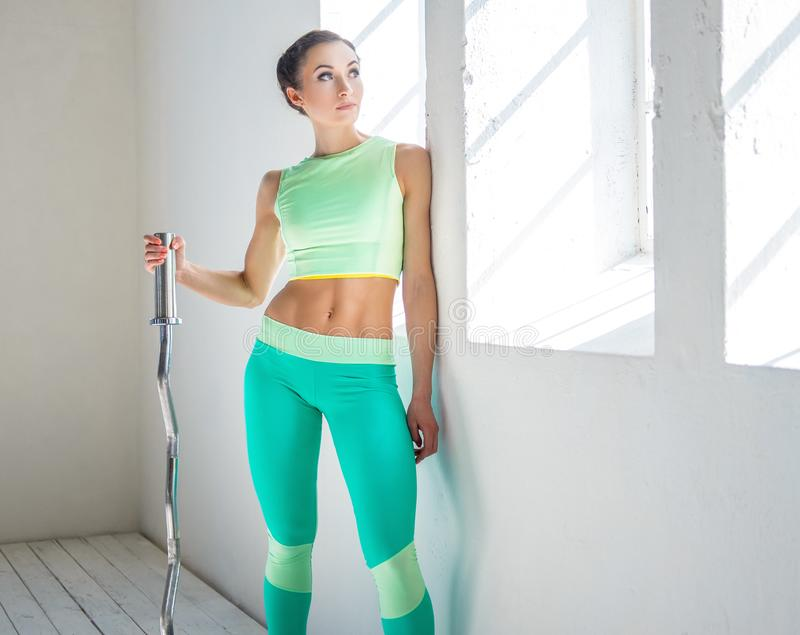 An athletic, sporty female dressed in an azure sportswear holds barbell. royalty free stock photos