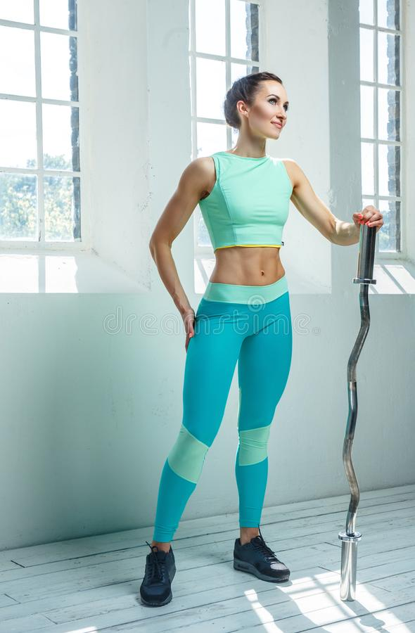 An athletic, sporty female dressed in an azure sportswear holds barbell. stock images