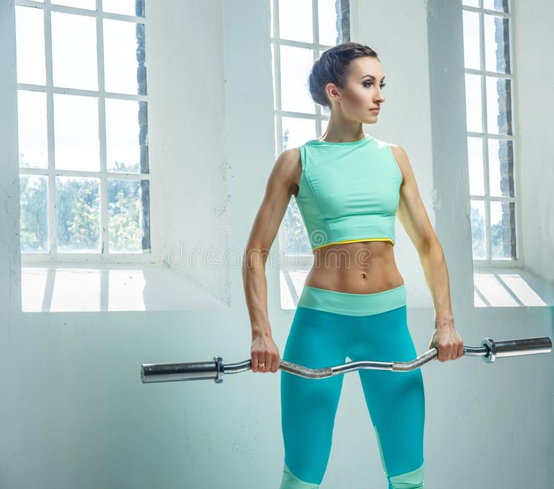An athletic, sporty female dressed in an azure sportswear holds barbell. royalty free stock photography