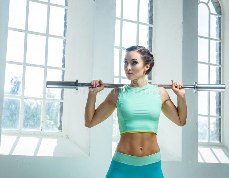 An athletic, sporty female dressed in an azure sportswear holds barbell. stock photo