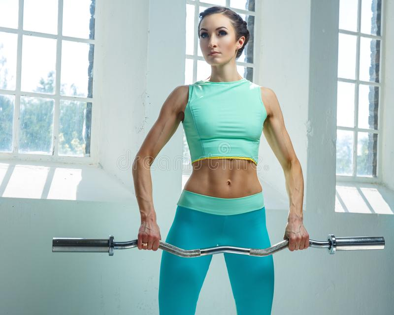 An athletic, sporty female dressed in an azure sportswear holds barbell. royalty free stock image