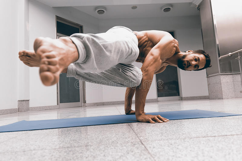 Download Athletic Strong Man Practicing Difficult Yoga Pose Stock Photo