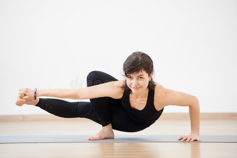 Strong woman smiling practicing complex yoga balancing handstand pose. Coach in action. Yoga indoors concept. Copy space stock images