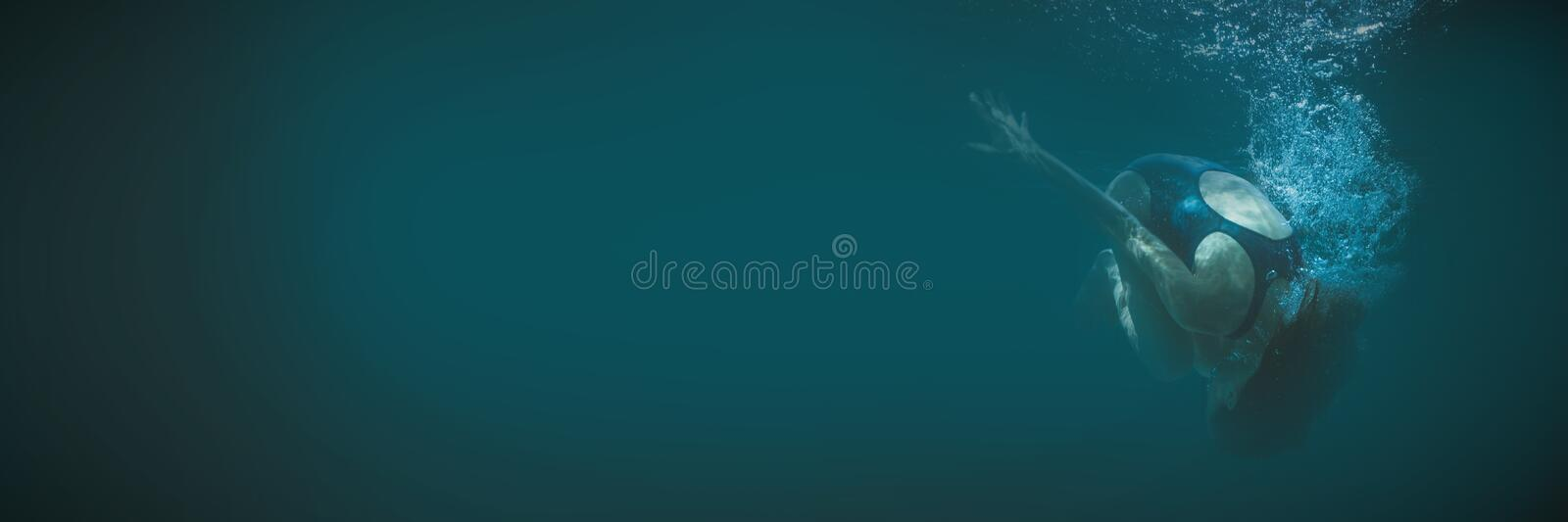 Athletic swimmer doing a somersault underwater stock photos