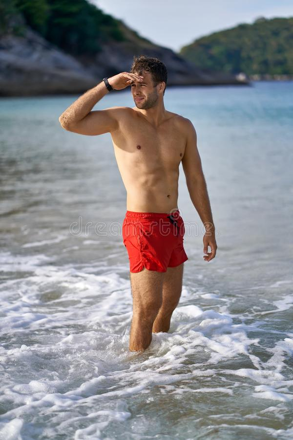 Tanned guy on beach. Athletic tanned man stands in the sea waves on the sunny nature background. He wears a red swim trunks and a dark watch. Guy holds his right stock images