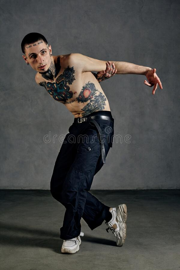 Athletic tattooed guy with naked torso, beard. Dressed in black pants and white sneakers. Dancing against gray. Athletic guy with tattooed body and face, naked stock photography