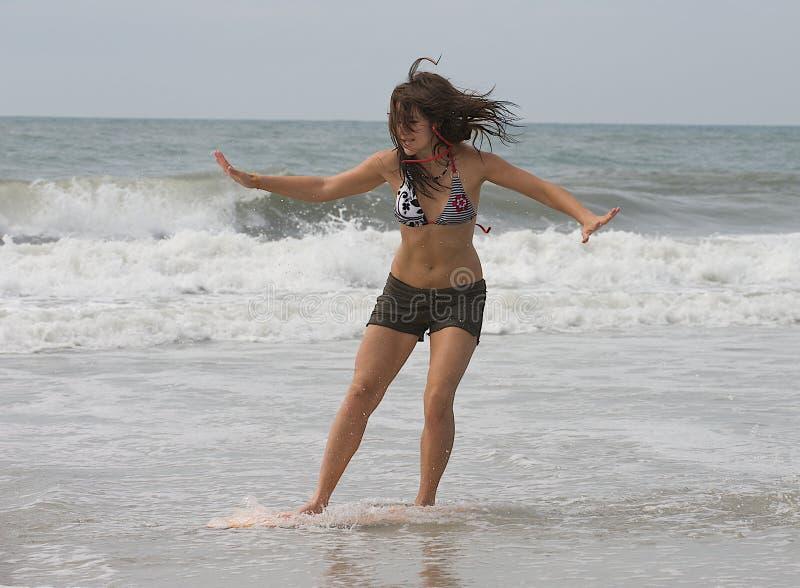 Athletic teen girl skim boarding at the beach stock photos