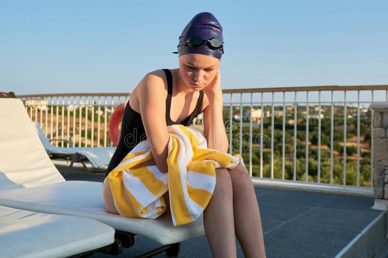 Athletic teenager girl in swimsuit and swimming cap with towel stock photo