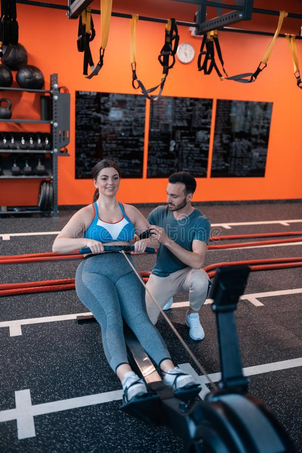 Athletic trainer helping his overweight client working out stock photos