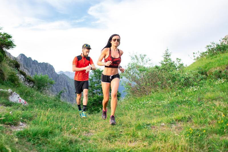 Athletic trainer measures the time of an athlete female race woman in the mountain stock image