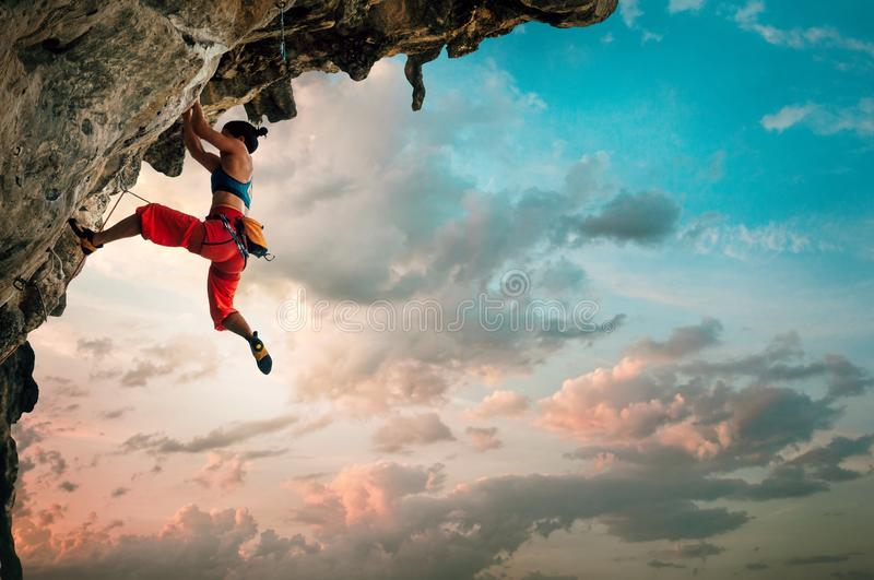 Athletic Woman climbing on overhanging cliff rock with sunrise sky background stock photography
