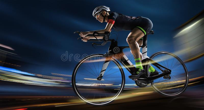Athletic woman cycling road bike in the evening. Sport background. Athletic woman cycling road bike in the evening. Dramatic view of the night city stock photography
