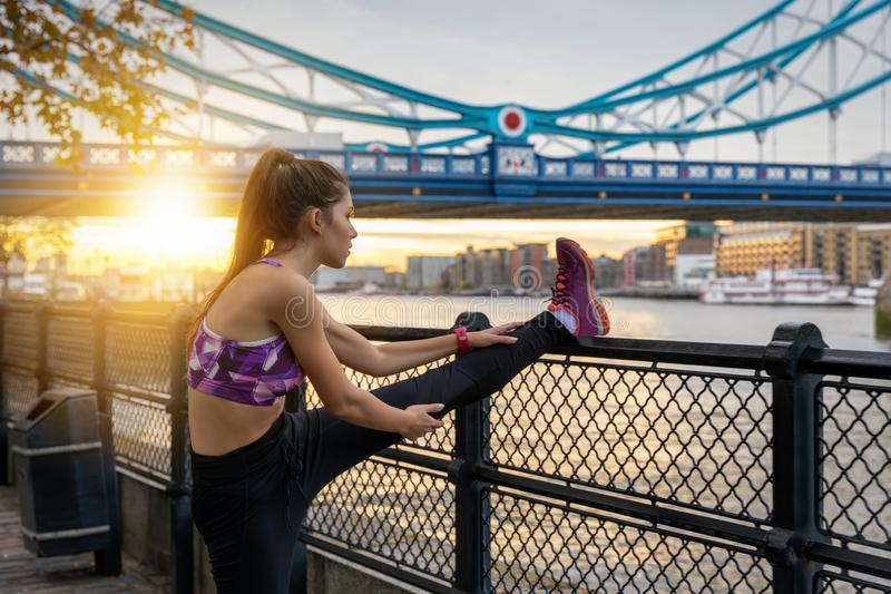 Athletic woman does her stretches after an early morning workou. T during sunrise in the city of London stock photo