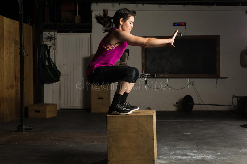 Athletic woman doing box jumps. Profile view of an athletic young woman jumping onto a box in a cross-training gym royalty free stock image