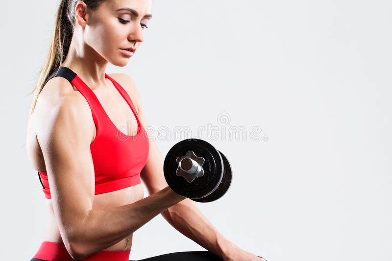 Athletic woman doing fitness workout with dumbbells on gray background. royalty free stock photos
