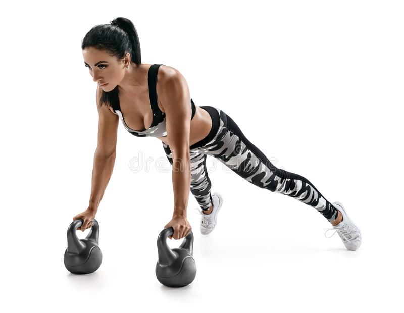 Athletic woman doing push ups exercise with kettlebells. Photo of latin woman in fashionable sportswear isolated on white background. Strength and motivation royalty free stock images