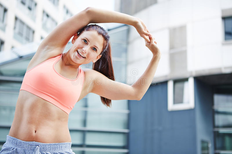 Athletic woman exercising in the city stock photo