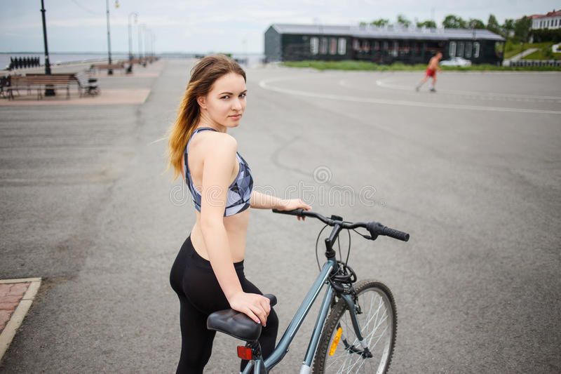 Athletic woman with long brown hair wearing a black leggins and sports top is standing onbicycle track. Empty space for. Young slender woman with long brown hair stock image