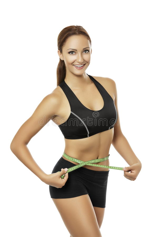 Athletic woman measuring her waistline. Beautiful young smiling woman with athletic body in black sportswear measuring her waistline over white background stock photography