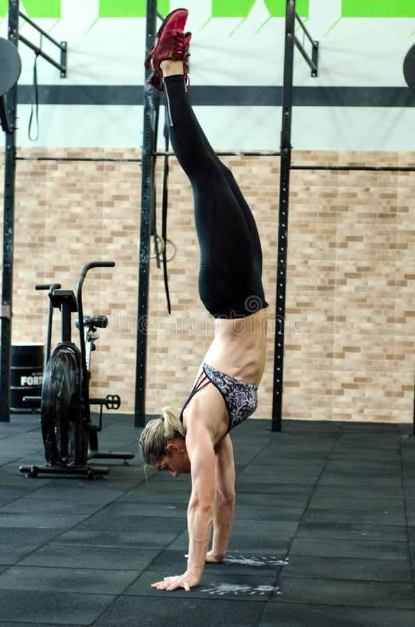 Athletic woman performing handstand stock image
