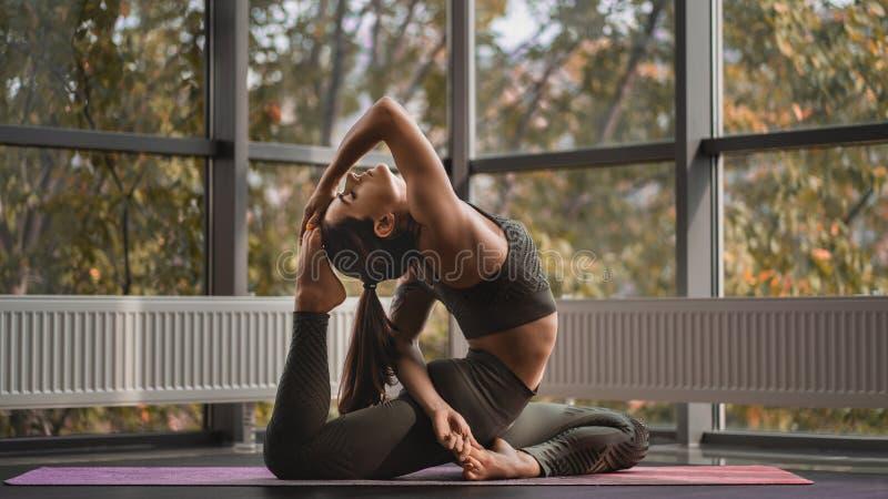Athletic woman practices yoga in the morning on balcony. One-legged king pigeon pose. Eka Pada Rajakapotasana. stock photography
