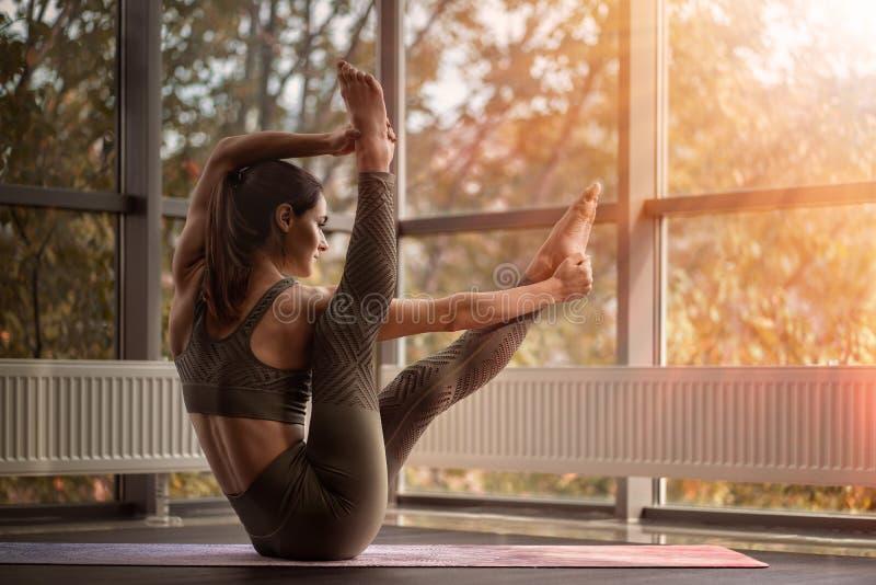 Athletic woman practices yoga. Sun shines through the window stock photo